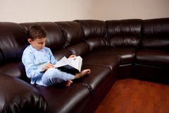 Cute kid reading a big book on a sofa. Cute schoolboy in pajamas reading a book while sitting on a leather sofa Stock Photos