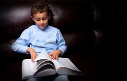 Cute kid reading a big book on a sofa. Cute schoolboy in pajamas reading a book while sitting on a leather sofa Royalty Free Stock Image