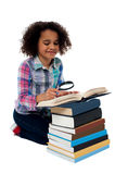 Cute kid reading book with magnifying glass Stock Photography