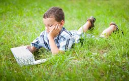 Cute kid reading a book outdoor. Cute kid reading a book while lying in grass Royalty Free Stock Images