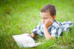 Cute kid reading a book outdoor. Cute kid reading a book while lying in grass Stock Image