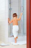 Cute kid ready to wash himself in shower Stock Photos