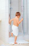 Cute kid ready to wash himself in shower. Cabin Stock Photo