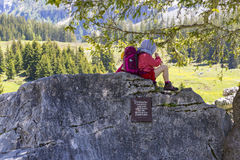 Cute kid resting on large rock near Oeschinensee Lake in Bernese Oberland, Switzerland Royalty Free Stock Photography