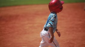 Cute kid running and sliding on home plate during baseball game