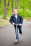Cute kid on scooter. Cute kid riding a scooter in a park Royalty Free Stock Photography