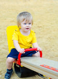Cute kid on the see saw. Little boy riding see-saw on the playground Stock Image