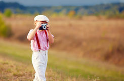 Cute kid shooting with old style photo camera Stock Photography