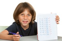 Cute kid showing notebook with math problems. Royalty Free Stock Image