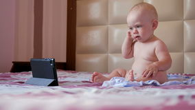 Cute kid sitting on the bed and stares cartoons on the tablet PC. Tiny one-year baby with no clothes stock video footage