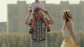Cute kid sitting on father is shoulders bend to kiss his mother stock video footage