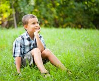 Cute kid sitting in grass. Cute kid relaxing outdoor in a grass field Royalty Free Stock Photo