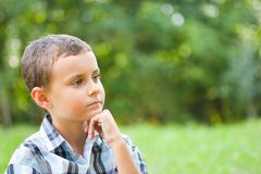 Cute kid sitting in grass. Cute kid relaxing outdoor in a grass field Royalty Free Stock Image