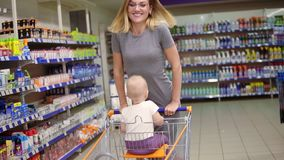 Cute kid is sitting in a grocery cart, while her mother is pushing the cart forward riding on it. Little baby and her stock video footage