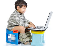 Cute kid sitting on toilet. With laptop royalty free stock photography