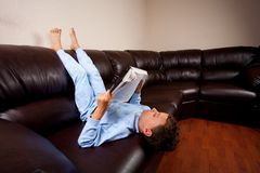 Cute kid sitting upside down reading a big book. Cute schoolboy in pajamas reading a book (a dictionary) while sitting on a sofa upside down Royalty Free Stock Photography