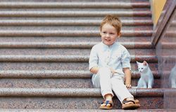 Cute kid and small kitten sitting on stairs Stock Image