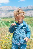 Cute kid smelling a flower in countryside stock photos