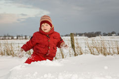 Cute Kid in Snow. Beautiful winter portrait of a cute little boy (4) in deep snow against a rural landscape Royalty Free Stock Images