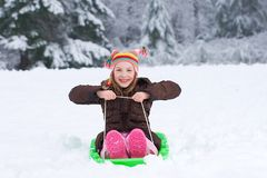 Cute kid on a snow sled Royalty Free Stock Photography