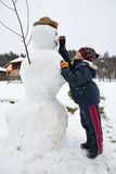 Cute kid and snowman Royalty Free Stock Photo