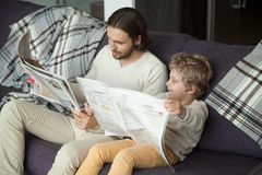 Cute kid son reading newspaper sitting on sofa with dad. Cute kid son holding newspaper sitting on sofa with dad, curious funny clever boy pretending reading stock image