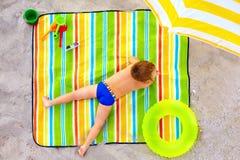Cute kid sunbathing on colorful beach Royalty Free Stock Images