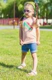 Cute kid in sunglasses. Cute kid in denim shorts and sunglasses  posing at camera Stock Photos