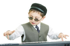 Cute kid in sunglasses playing piano Stock Images
