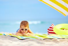 Cute kid in sunglasses resting on beach Stock Photo