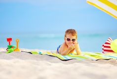 Cute kid in sunglasses resting on beach Stock Images