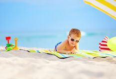 Cute kid in sunglasses resting on beach Stock Photos