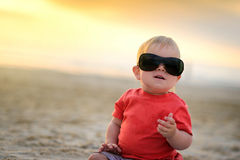 Cute kid in sunglasses sitting on sand Royalty Free Stock Photo