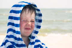 A cute kid in a terry dressing gown with atopic dermatitis, squinting. A child with dry red skin on his face, an allergy.  Stock Photo