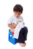 Cute kid with toilet paper on toilet. Cute kid is sitting on toilet and holding toilet paper Royalty Free Stock Images