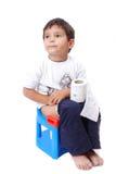 Cute kid with toilet paper on toilet. Cute kid is sitting on toilet and holding toilet paper Stock Photo
