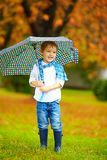 Cute kid with umbrella in park, rainy weather Stock Images