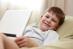 Cute kid using laptop computer smiling Stock Photo