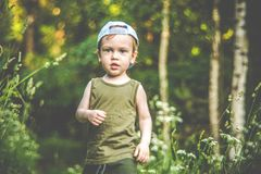 Cute kid walking in forest alone royalty free stock image