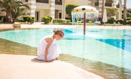 Cute kid walking by the pool royalty free stock photos