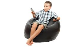 Cute kid watching tv. Sitting in a very comfortable and soft sack chair, with a remote control in his hand Stock Photography