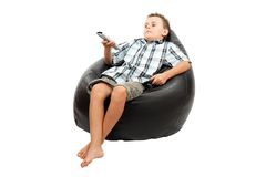 Cute kid watching tv. Sitting in a very comfortable and soft sack chair, with a remote control in his hand Royalty Free Stock Photo