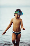 Cute kid wearing mask and trunks in sea stock photography