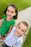 Cute Kids. Two little kids holding hands as they walk down the sidewalk.  Plenty of copy space for your text Stock Photo