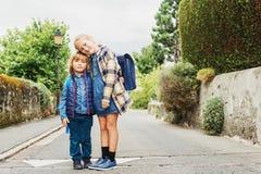 Little kids portrait. Cute kids with backpacks walking to school Stock Image
