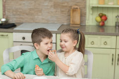 Free Cute Kids Baked Cookies And Tasting It At The Table In The Home Kitchen Royalty Free Stock Images - 87669599
