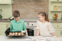 Cute kids baked cookies and tasting it at the table in the home kitchen Stock Photography