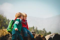 Cute kids -boy and girl -sharing a joke while travel in mountains. Family hiking stock photography