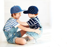 Cute kids, brothers in denim jumpsuits communicating, indoors Stock Photo