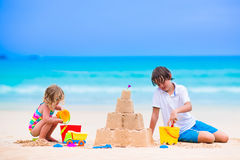 Cute kids building sand castle on the beach. Kids playing on a beach. Two children build a sand castle at the sea shore. Family vacation on a tropical island stock photography